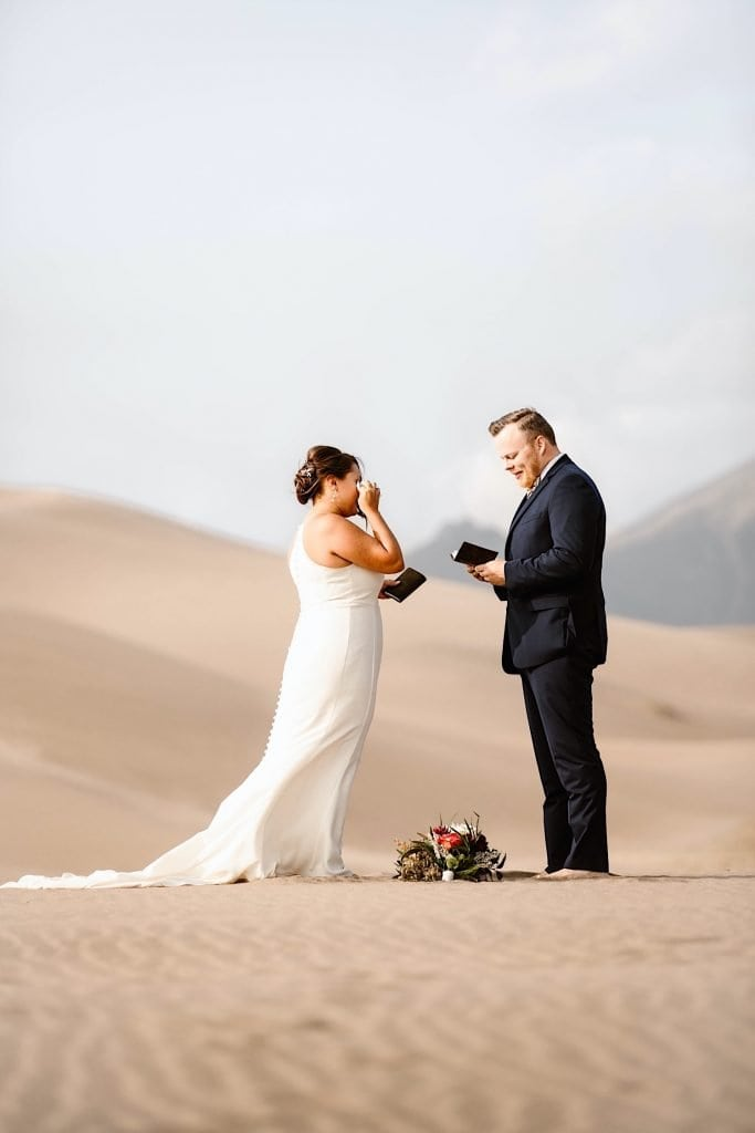 bride wiping tear from her eye during her Great Sand Dunes National Park elopement ceremony