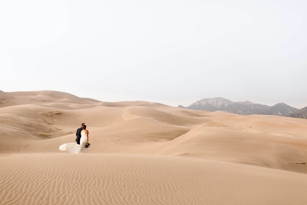 bride and groom walking away from their Great Sand Dunes National Park elopement ceremony site