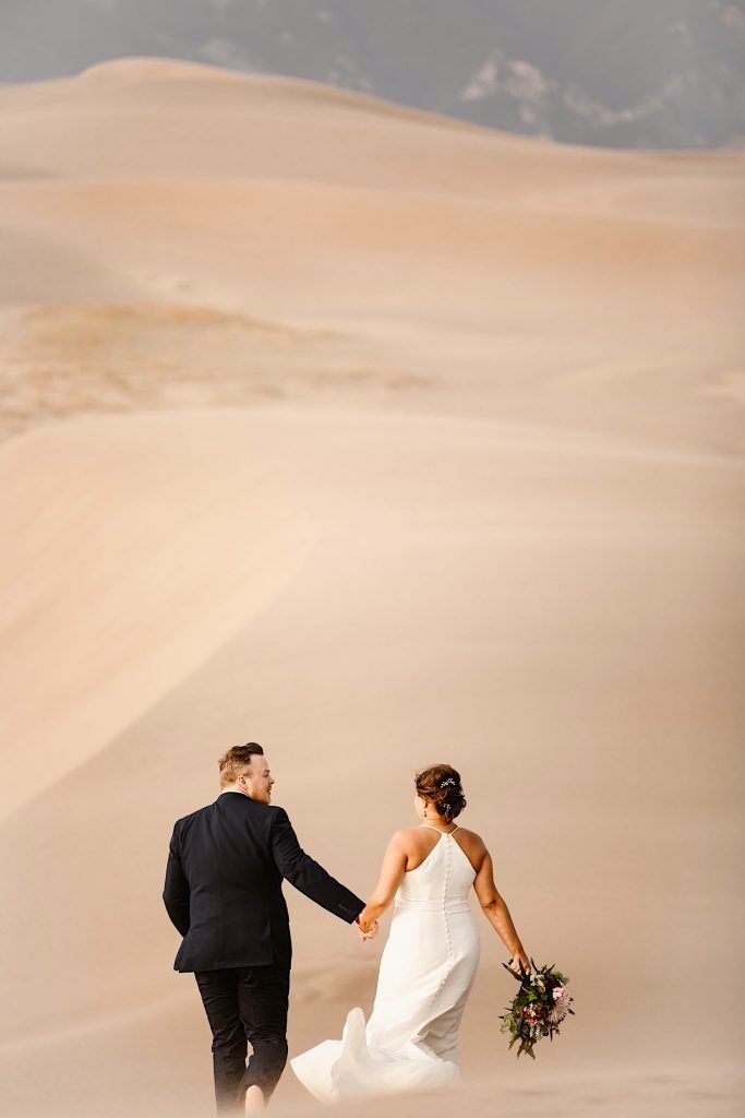 bride and groom trekking across the dune field after their Great Sand Dunes National Park elopement ceremony