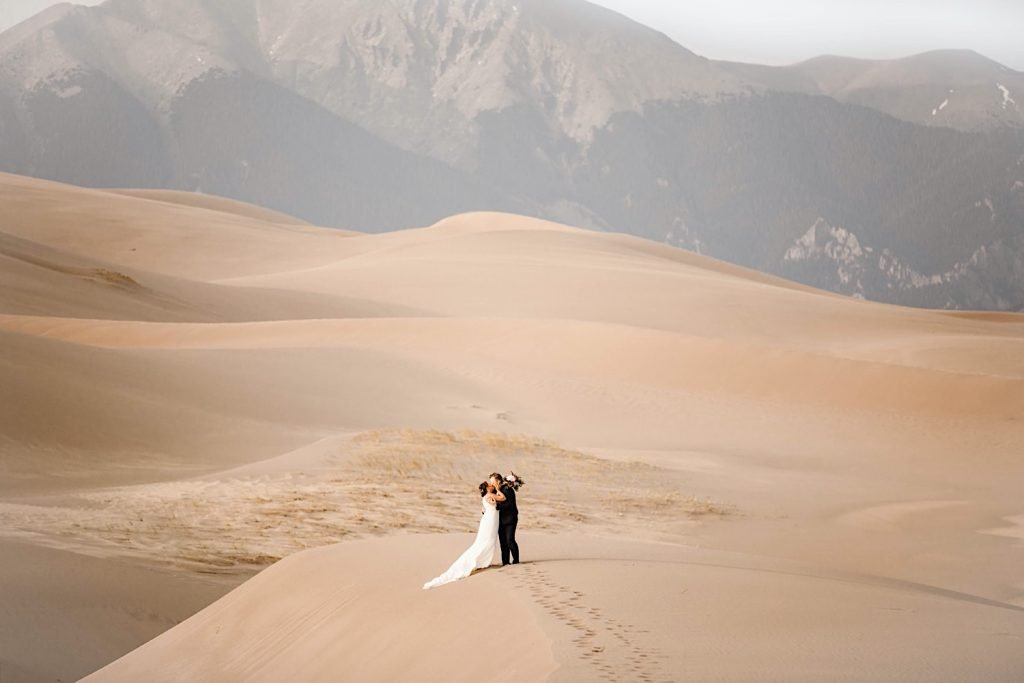 Great Sand Dunes National Park elopement photo of the bride kissing the groom on the dune field
