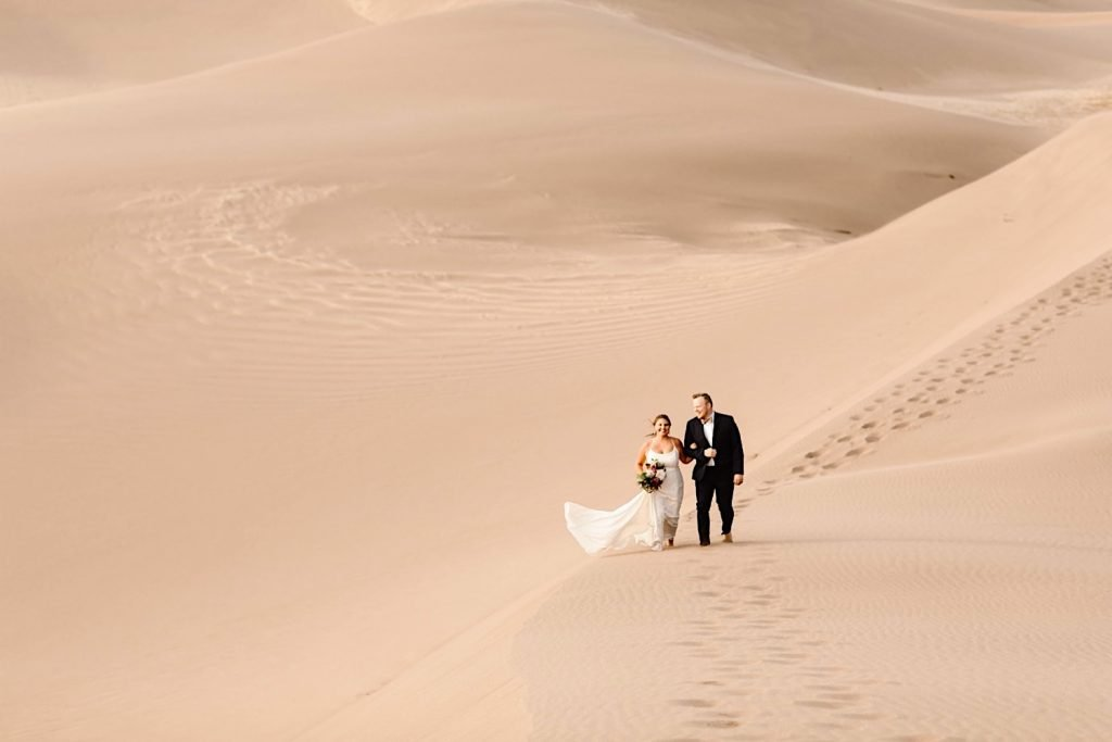 bride and groom hiking through sand during their Great Sand Dunes National Park elopement