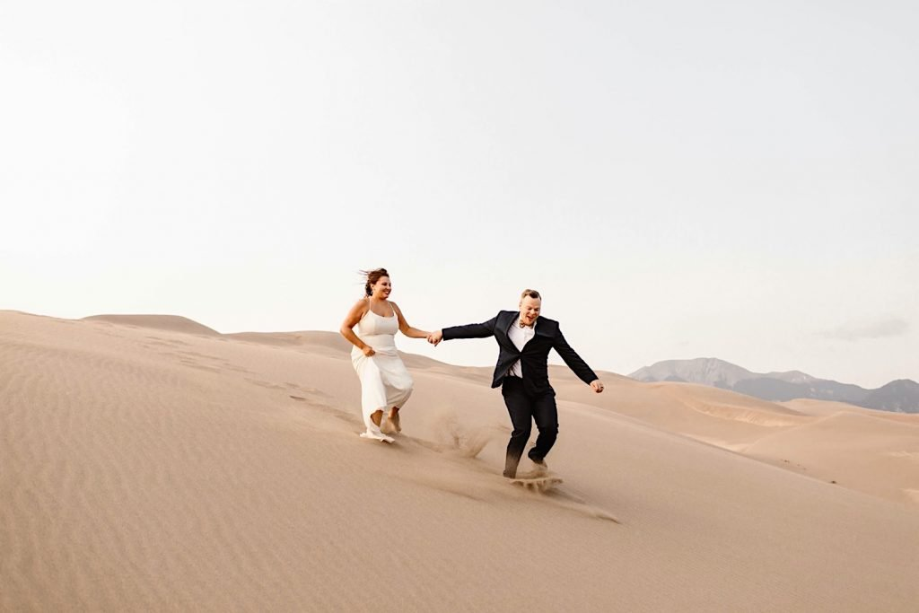 Great Sand Dunes National Park elopement couple racing down a sand dune