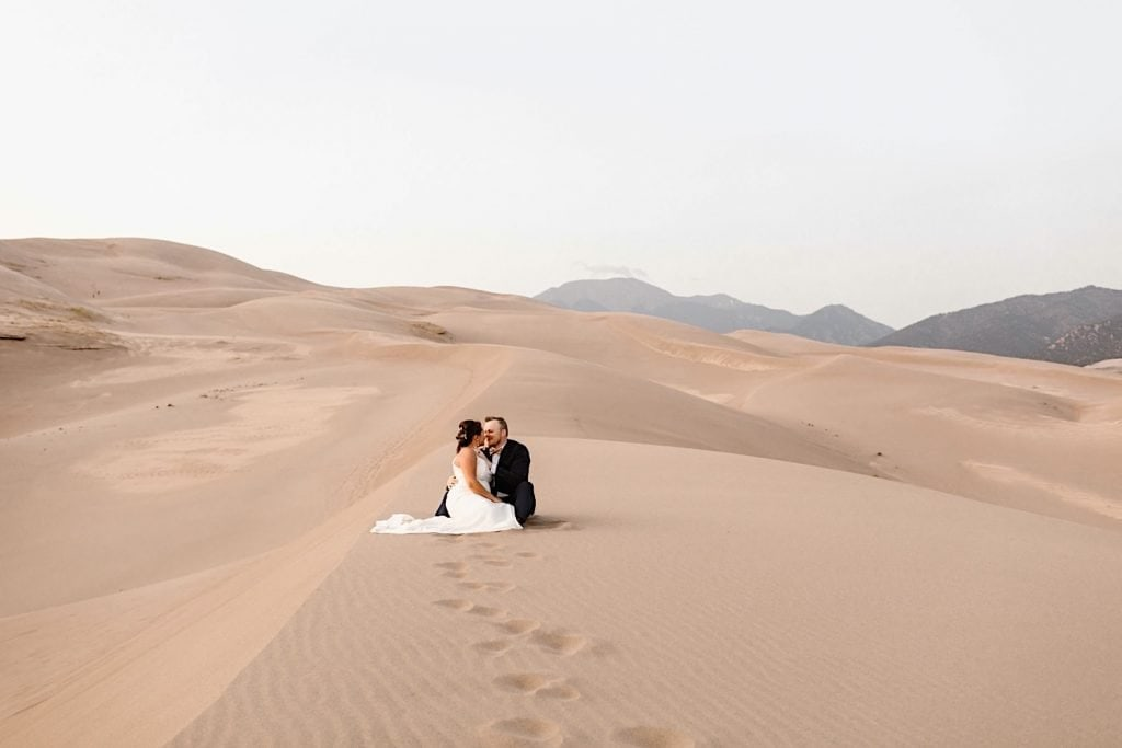 bride and groom sitting down on the sand during their Great Sand Dunes National Park elopement wedding