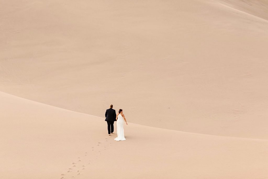 eloping couple walking across the sand dunes