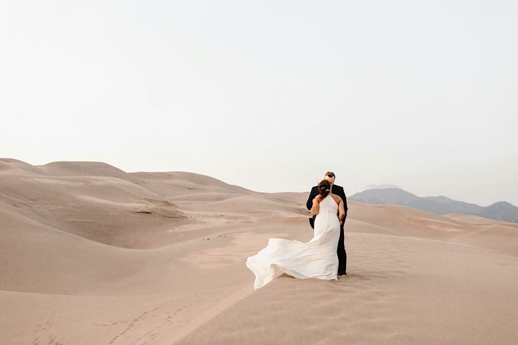 couple kissing on the edge of a dune during their Great Sand Dunes National Park elopement