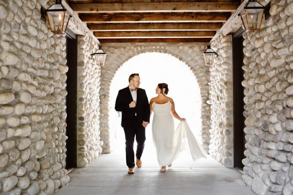 cancel wedding and elope | couple walking through a tunnel in their wedding attire