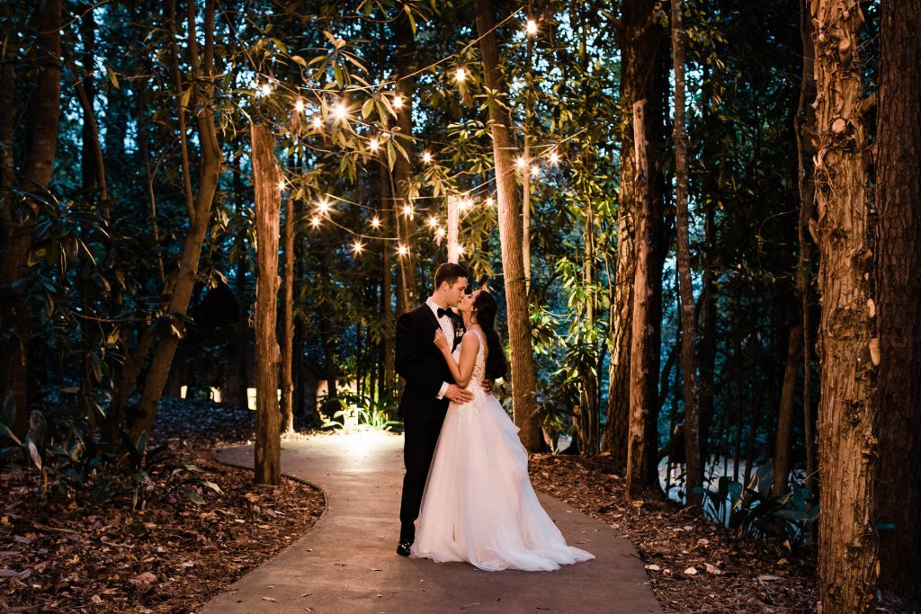 couple getting married in the woods with twinkle lights above their heads