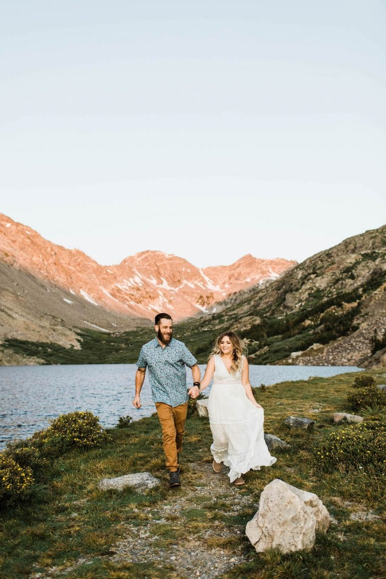 couple running hand in hand down a trail by an alpine lake during their Colorado elopement morning