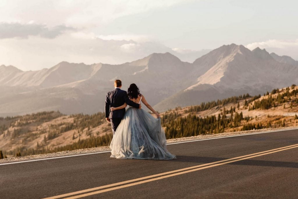 couple walking down a mountain pass at sunset while being photographed by a Colorado adventure elopement photographer