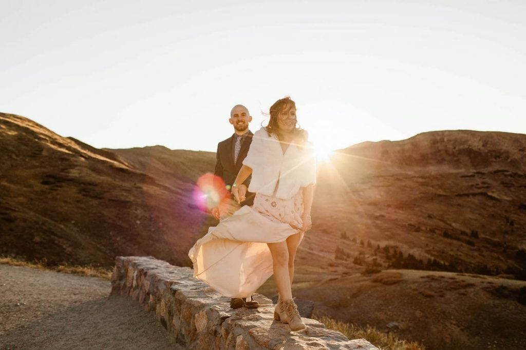 couple walking together in the mountains at sunset while being photographed by a Colorado adventure elopement photographer
