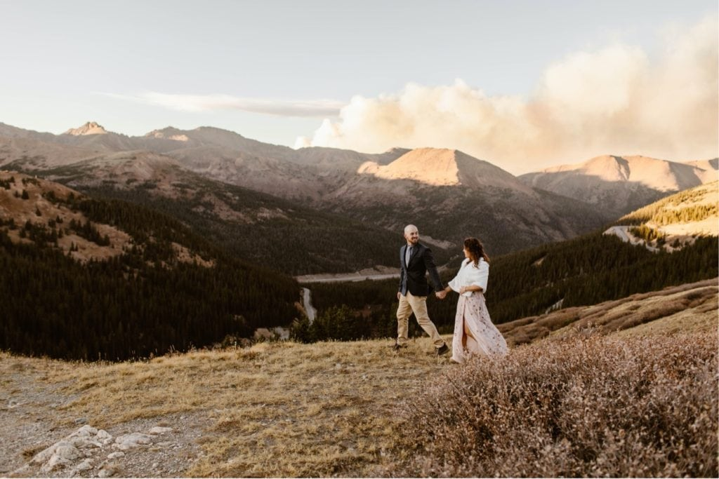 bride and groom walking hand in hand in the mountains while the smoke of a wildfire emerges from behind them
