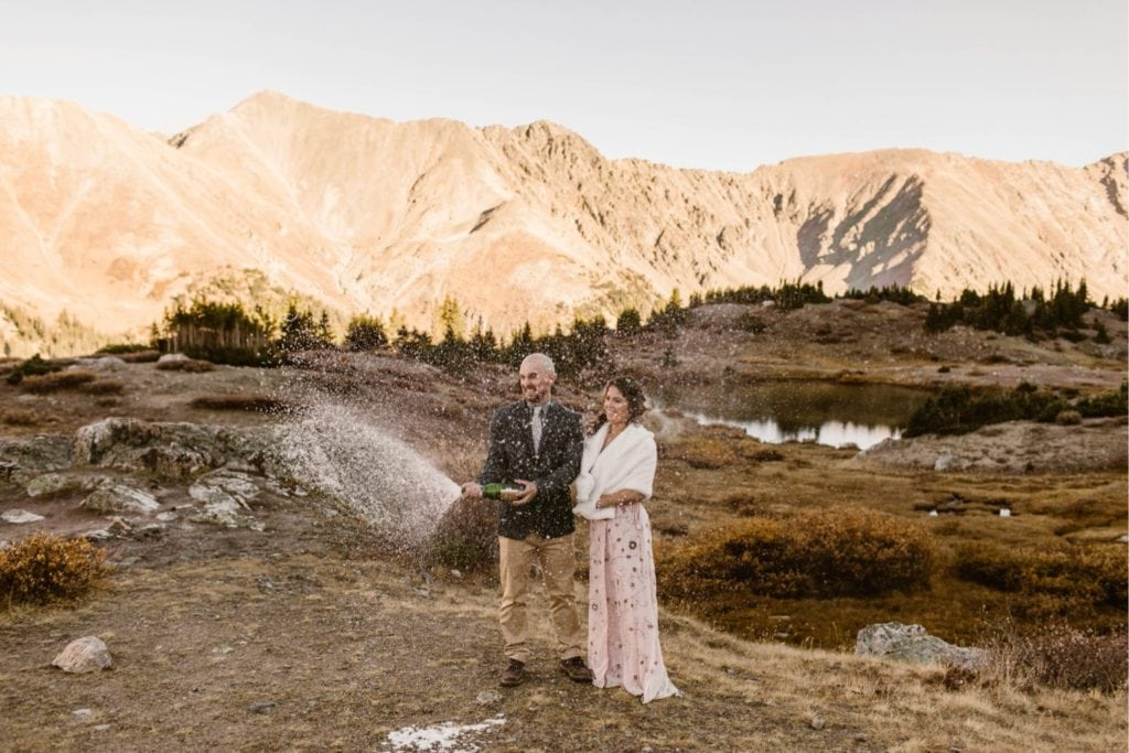 couple popping champagne at their Colorado micro wedding in the mountains near Denver
