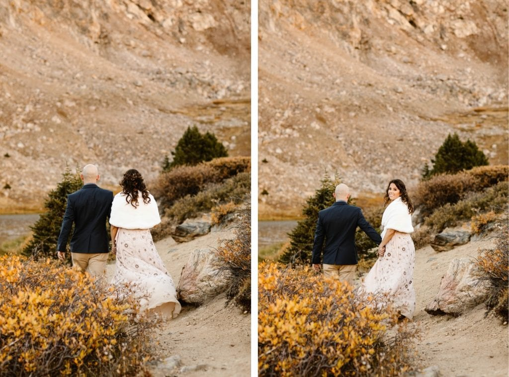 eloping couple walking together down a hiking trail after their Colorado micro wedding ceremony