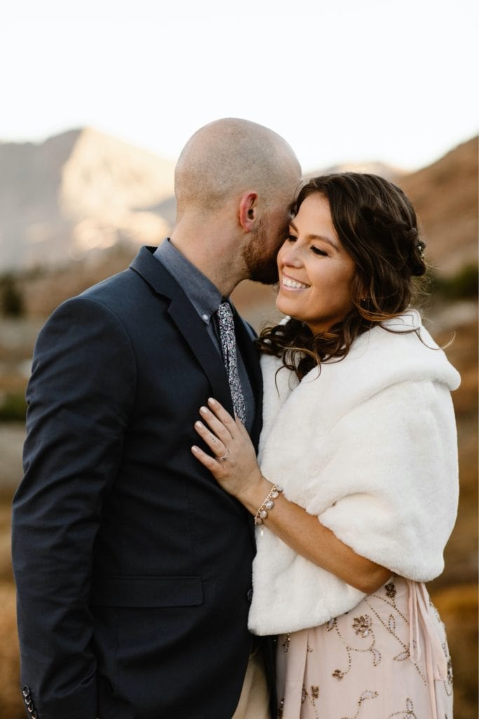 groom whispering funny jokes into bride's ear while they stand together to stay warm in the mountains of Colorado