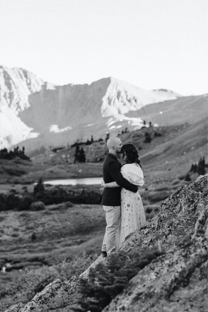 Colorado micro wedding couple standing together and admiring the alpenglow on the mountains at sunset