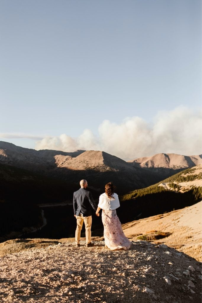 couple standing together on an overlook in the mountains while looking out a plume of wildfire smoke in Colorado
