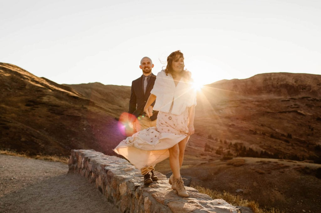 eloping couple walking on a stone wall in the mountains at sunset after their Colorado micro wedding ceremony