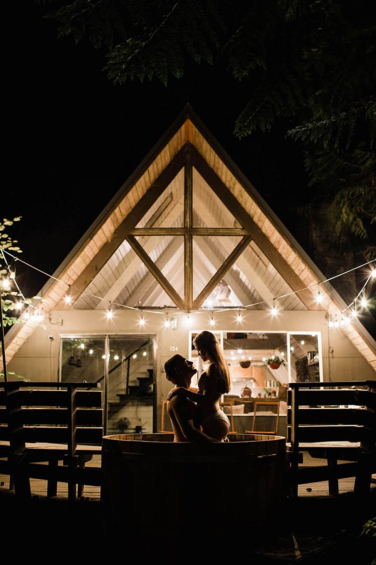 couple taking a soak in the hot tub outside their cabin the night before their adventure elopement photographed by Colorado elopement photographers Sheena Shahangian Photography LLC