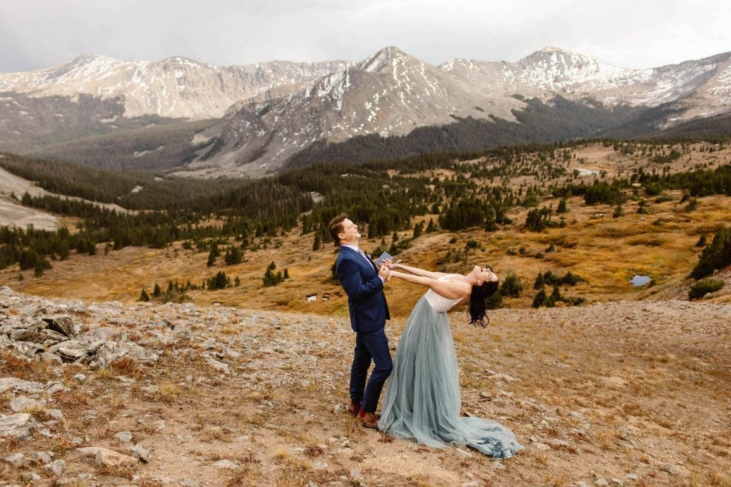 recently married eloping couple screaming up at the sky after pronouncing themselves married in the Rocky Mountains while a Colorado elopement photographer takes photos