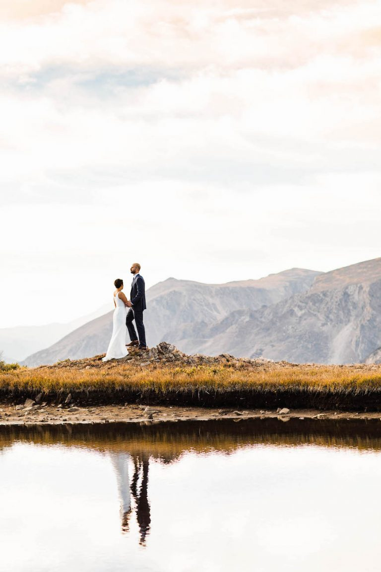 couple standing hand in hand looking out at the mountains during their adventure elopement in the Rocky Mountains of Colorado