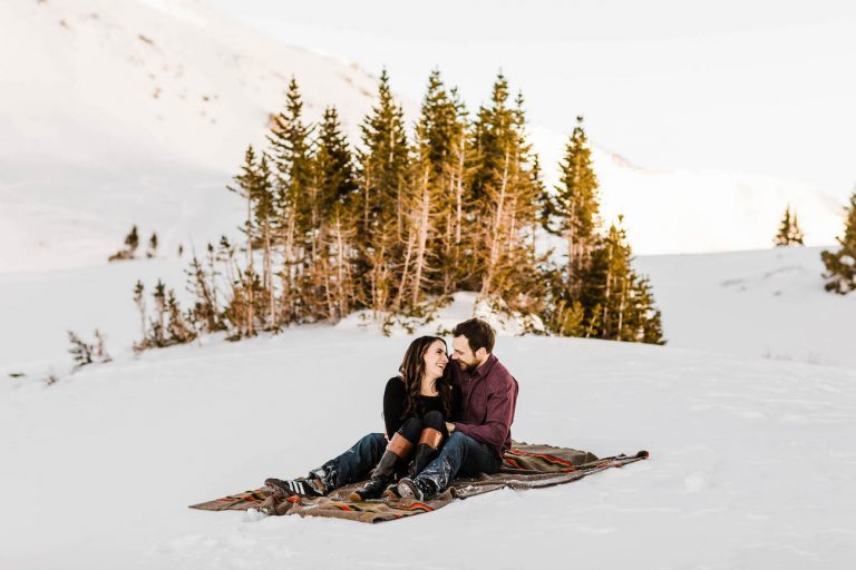 Colorado elopement photographers documenting adventure elopement couple snuggling on a blanket in the snow before their adventure wedding