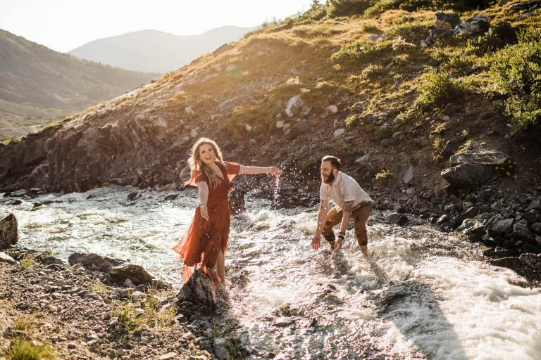 couple splashing in a river in the Rocky Mountains before their adventure elopement documented by Sheena Shahangian Photography LLC Colorado elopement photographers