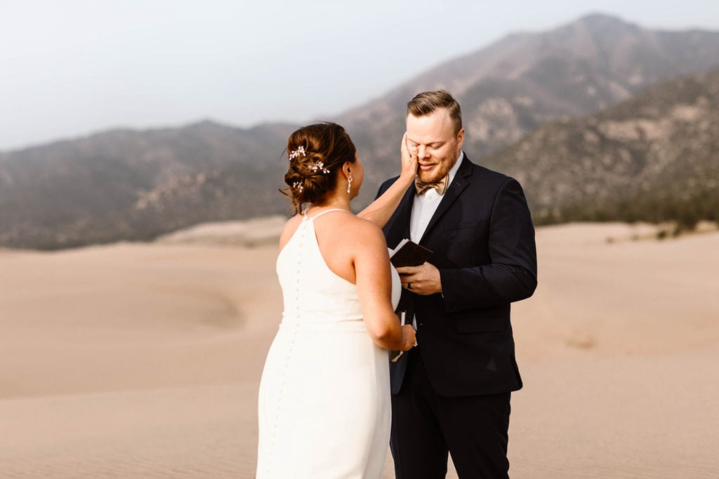 couple reading the elopement vows they wrote to each other for their wedding ceremony