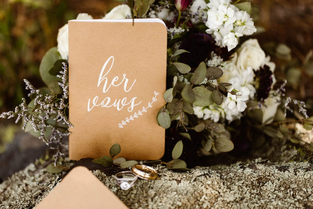 elopement vows book leaning on a bouquet