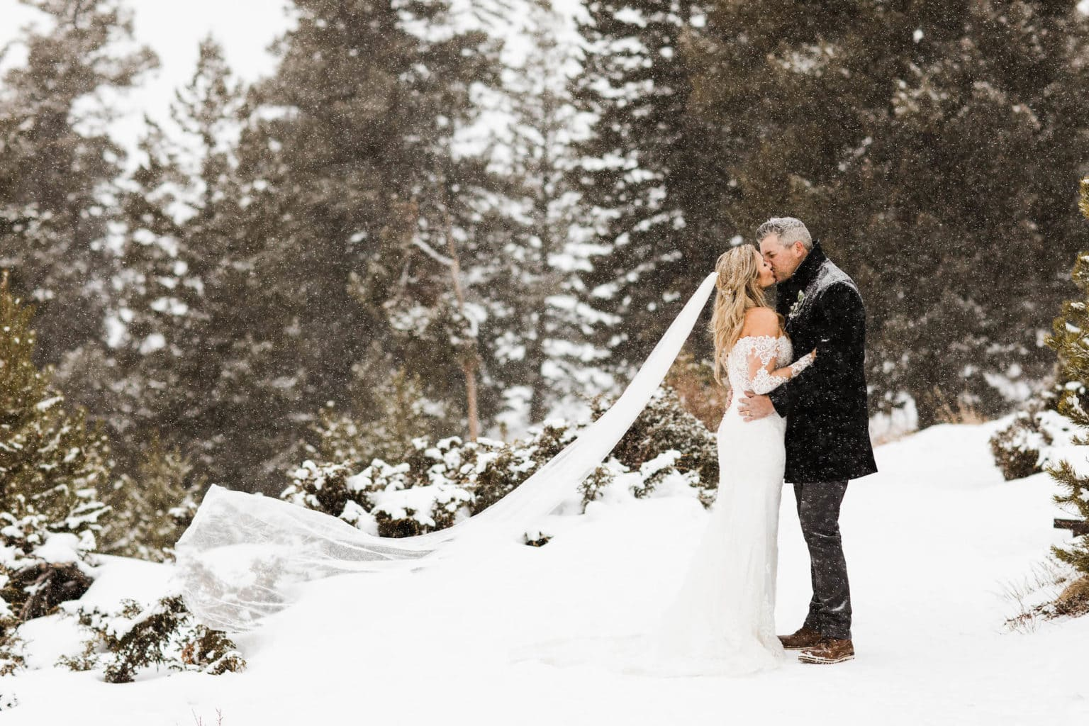 winter elopement couple kissing in the snow