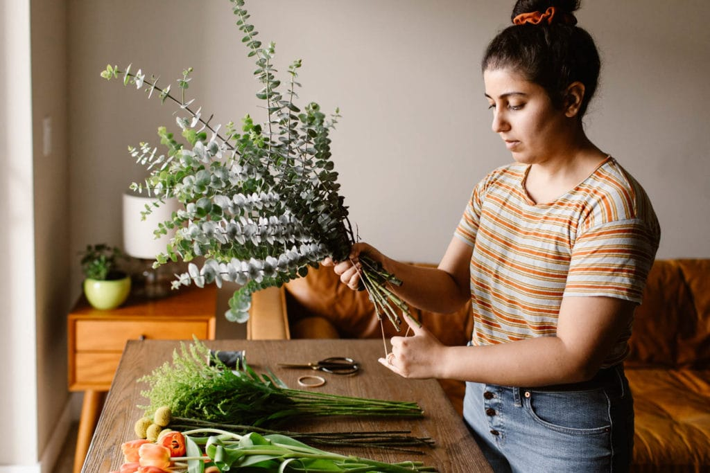 woman adding eucalyptus from Trader Joes to a diy wedding bouquet