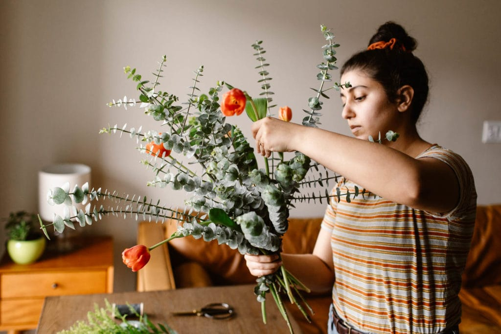 woman adding colorful boho flowers from Trader Joes to a diy wedding bouquet