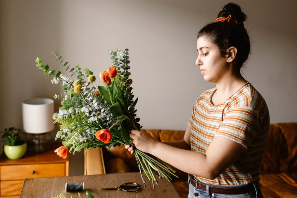 woman showing how to secure a diy bouquet with green floral tape