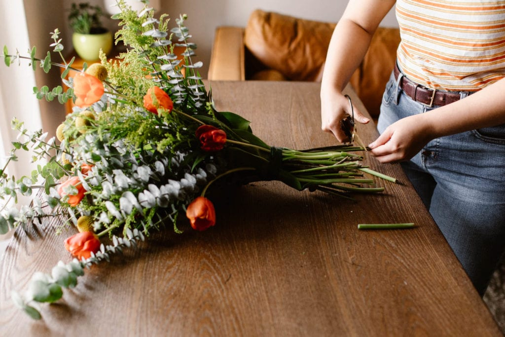 woman showing how to trim the stems on a diy elopement wedding bouquet