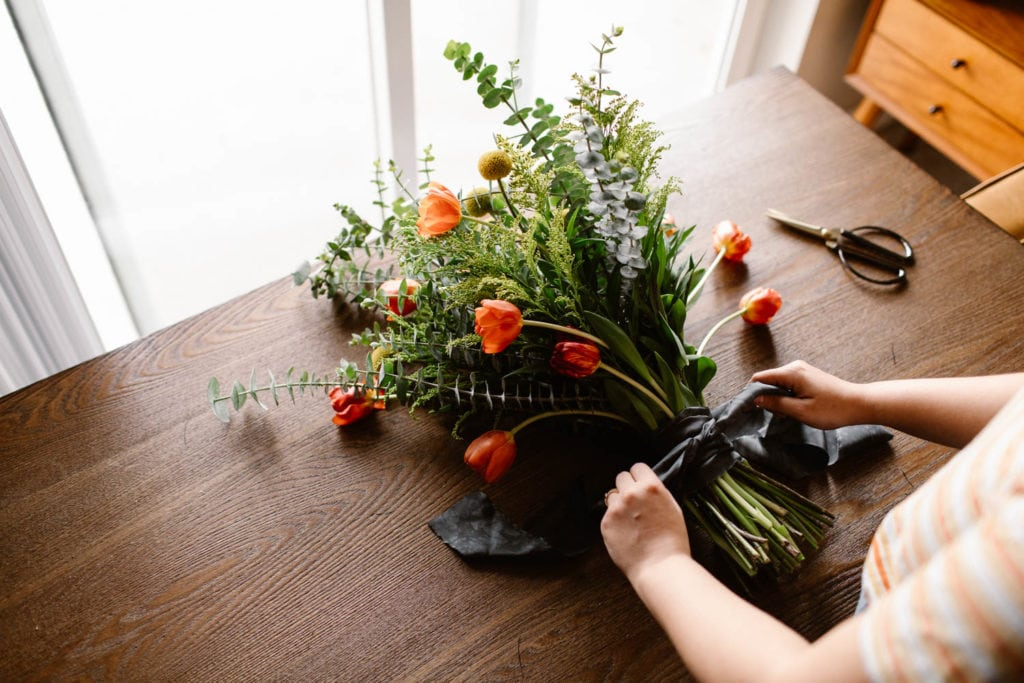 woman showing how to tie a ribbon around a diy wedding bouquet
