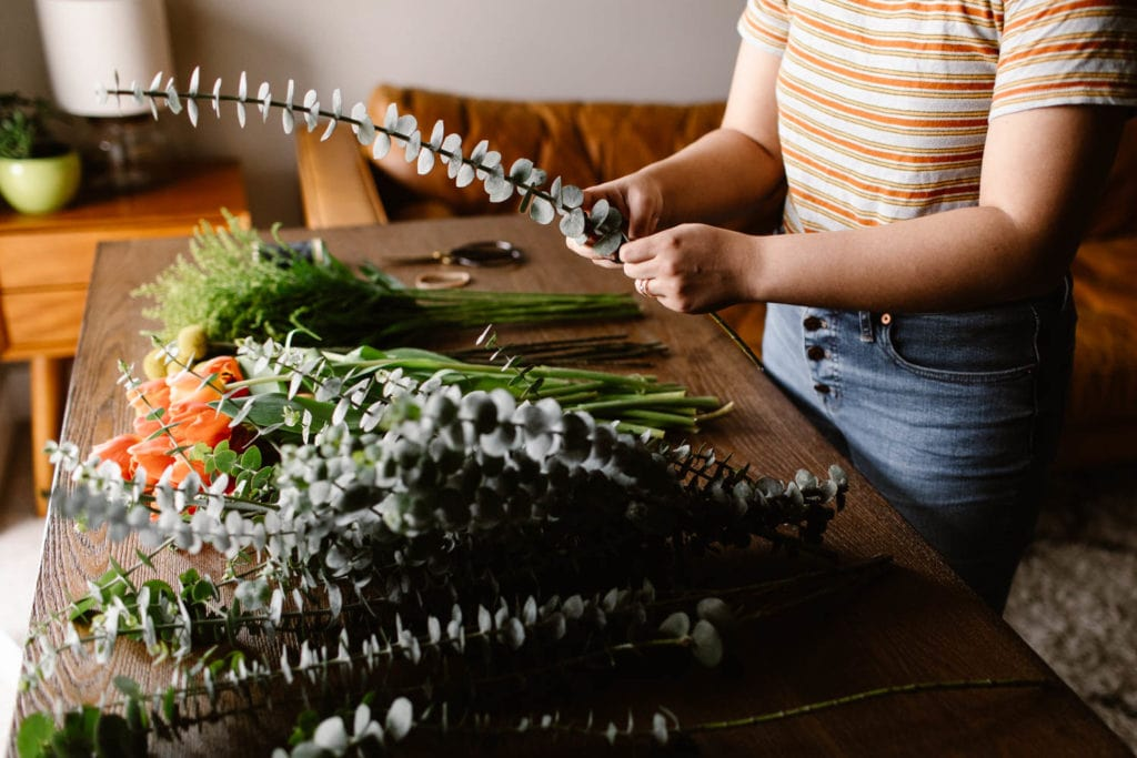 woman showing how to prep the stems for a diy wedding bouquet