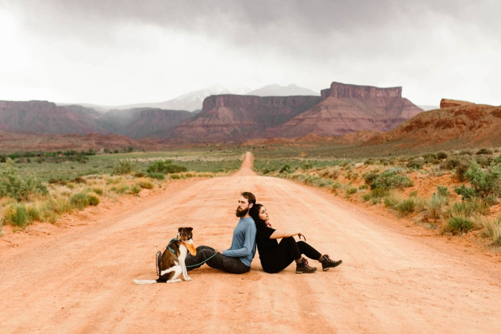 best things to do in Moab Utah cover photo of a couple sitting on a desert dirt road off Utah 128