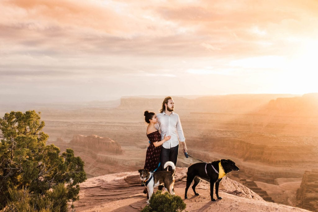 couple standing at overlook in Dead Horse Point Moab Utah at sunset
