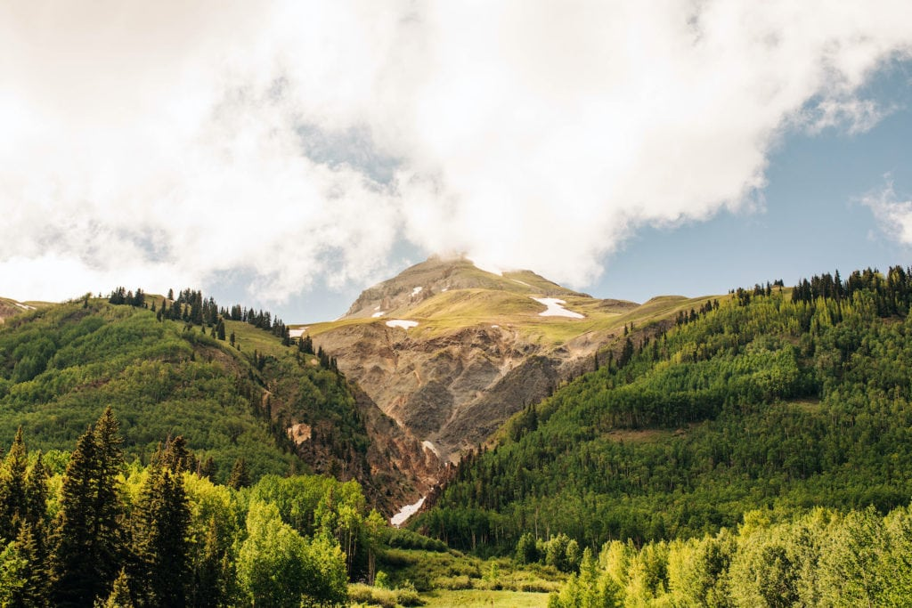 view of clouds forming over a mountain during the best time to visit Colorado in the summer